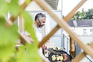 Man barbecuing on his balcony - MBEF001278