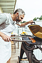 Man barbecuing on his balcony - MBEF001281