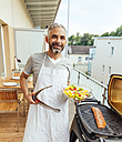 Portrait of smiling man with bowl of salad and tongs on his balcony - MBEF001283