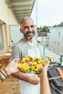 Portrait of smiling man barbecuing on his balcony with woman's hands holding salad bowl in the foreground - MBEF001284