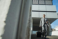 Businessman with suitcase outside office building - UUF001950
