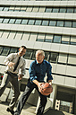 Two businessmen playing basketball outside office building - UUF001959