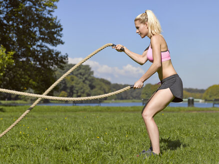 Germany, Young woman doing sports with ropes - MAD000003