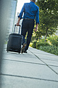 Businessman with suitcase and headphones walking on pavement - UUF001966