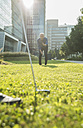 Two businessmen playing golf outside office building - UUF001971