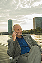 Germany, Frankfurt, businessman using cell phone at river Main - UUF001979