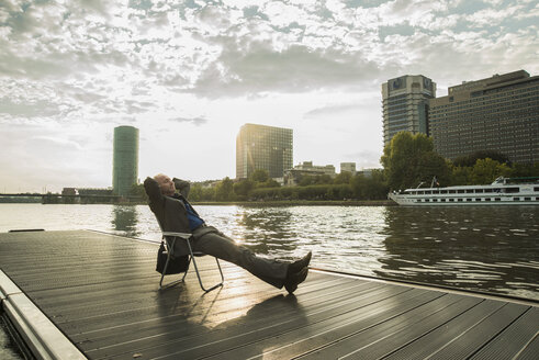 Germany, Frankfurt, relaxed businessman at river Main - UUF001990