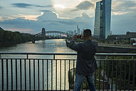 Germany, Frankfurt, man on bridge taking a picture - UUF001993