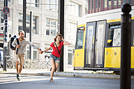 Germany, Berlin, Young couple running in street - FKF000693