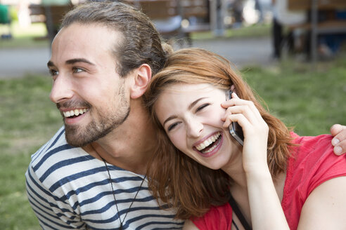 Germany, Berlin, Young couple walking in park, using smart phone - FKF000653