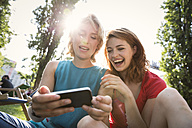 Germany, Berlin, Young women using smart phone in park - FKF000656