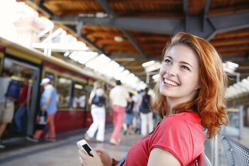 Germany, Berlin, Young woman using smart phone at train station - FKF000659
