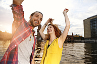 Germany, Berlin, Young couple enjoying sunset at Spree river - FKF000674