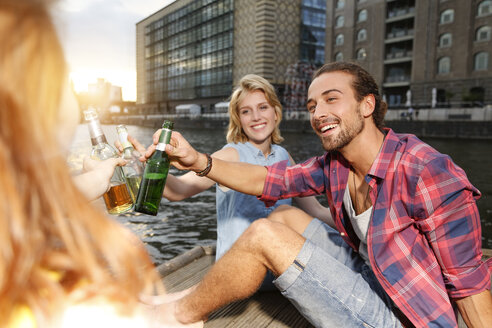 Germany, Berlin, Friend sitting at Spree river, drinking beer - FKF000681