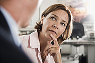 Serious woman looking at businessman - UUF001909
