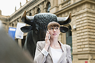 Germany, Hesse, Frankfurt, portrait of telephoning businesswoman in front of stock market - FMKYF000527