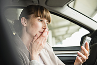Portrait of businesswoman sitting in a car looking at her smartphone with hand on her mouth - FMKYF000531