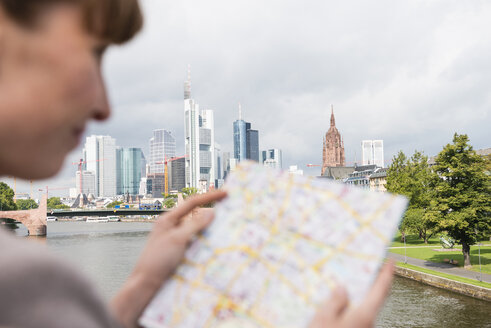 Germany, Hesse, Frankfurt, businesswoman reading city map - FMKYF000556