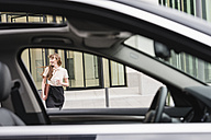 Germany, Hesse, Frankfurt, happy businesswoman walking with coffee to go behind a car - FMKYF000562