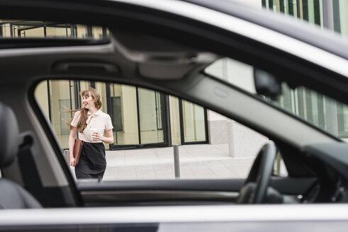 Germany, Hesse, Frankfurt, happy businesswoman walking with coffee to go behind a car - FMKYF000562