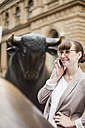 Germany, Hesse, Frankfurt, smiling businesswoman telephoning with smartphone in front of stock market - FMKYF000565