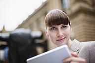 Germany, Hesse, Frankfurt, portrait of smiling businesswoman with digital tablet in front of stock market - FMKYF000568