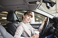 Germany, Hesse, Frankfurt, portrait of smiling businesswoman with coffee to go sitting in her car - FMKYF000574