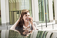 Germany, Hesse, Frankfurt, portrait of smiling businesswoman telephoning with smartphone - FMKYF000579