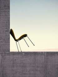 Chair leaning at concrete wall in front of sky, 3D Rendering - UWF000188