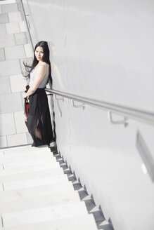 Young female Asian with violin standing on stairs - MAD000016
