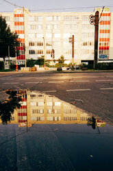 Germany, Berlin, facade of a commercial house reflected in a puddle - ZMF000380