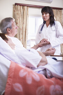 Doctor consoling senior man lying in hospital bed - ZEF000949