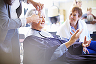 Female hairdresser cutting hair of senior woman - ZEF001015