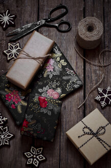 Wrapped christmas gifts, decoration, scissors and string on wooden table - CZF000171