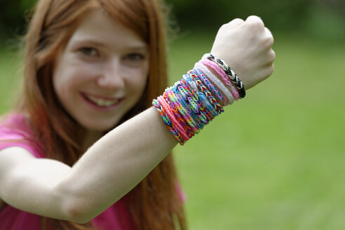 Smiling girl showing self-made looms at her wrist - LBF000957