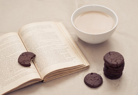 Bowl of white coffee, chocolate cookies and an old cook book - CZ000173