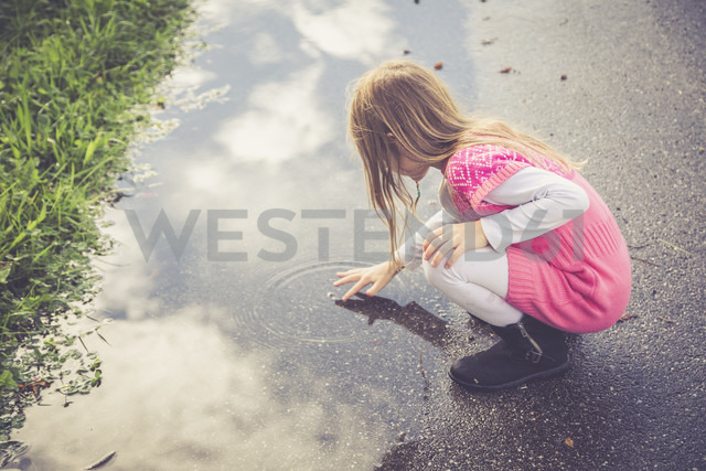 Little girl playing with water of a puddle - SARF000860