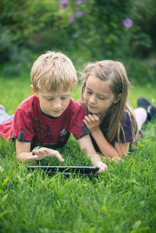 Brother and sister lying on a meadow using digital tablet - SARF000865