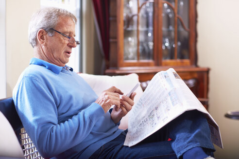 Senior man with telephone reading newspaper at home - ZEF001049