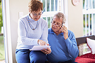 Senior couple reading document at home - ZEF001059