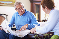 Senior man with newspaper at home talking to wife - ZEF001065