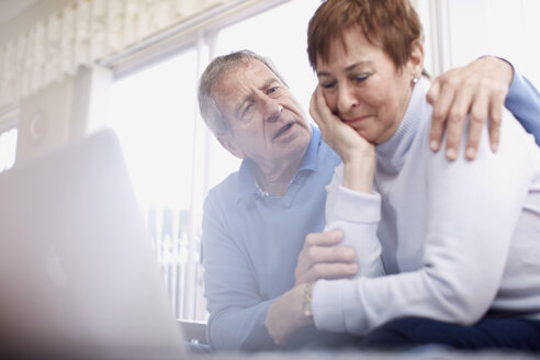 Senior man consoling crying wife at laptop - ZEF001076