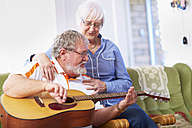 Senior man with wife at home playing guitar - ZEF001101