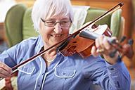 Senior woman at home playing violin - ZEF001103