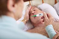 Senior woman taking temperature of sick husband at home - ZEF001153