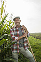 Portrait of smiling farmer standing besides a maize field - UUF002020