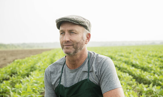 Portrait of farmer standing in front of a field - UUF002025