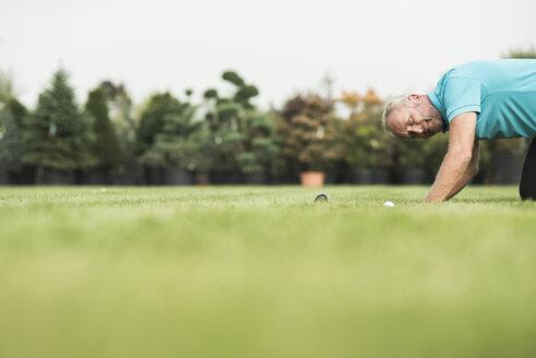 Golf player kneeling on turf looking at golf ball - UUF002040