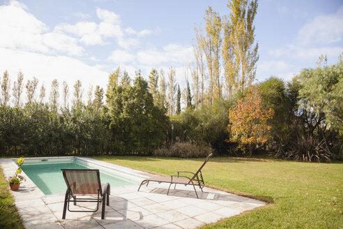 Deckchairs at poolside in garden - WESTF020077