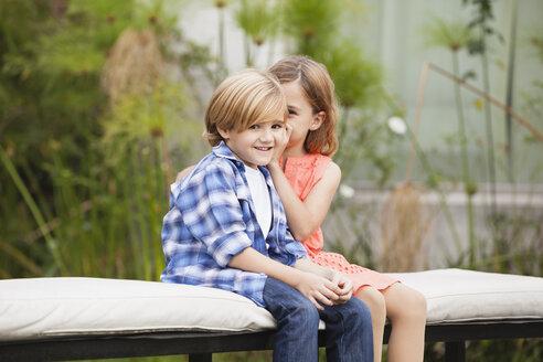 Girl whispering into boy's ear - WESTF020095